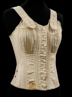1890 girl's corset made of unbleached cream wool. Made in two halves joined at the center back and at the front with mother-of-pearl buttons attached to very long cotton threads. It reaches from the shoulder where there are adjustable wool shoulder straps to the hip. It is boned at the center front and back, but the bands of stiffening  is achieved with inserted cords and tapes. It is only slightly shaped at the hip and waist but there are narrow pleated gussets for the breasts.