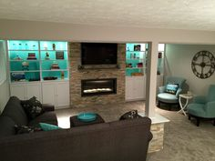 Custom built in white cabinets, Tiffany blue, gray, oversized clock, gas contemporary fireplace, sectional, support pole post table, Desert Quartz ledge stone, cozy, comfy