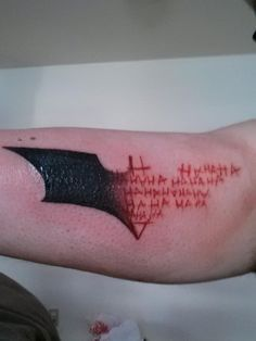 Batman symbol tattoo transitioning into Joker madness