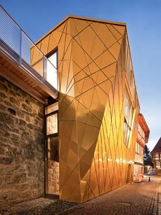 Berlin studio Gnädinger Architekten has completed a faceted golden museum dedicated to medieval marksmanship beside the fortified city wall of Duderstadt in Germany.