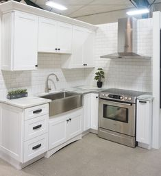 White cabinets, shaker door style, white marble countertops, white bevelled subway tile, stainless steel farmhouse sink.