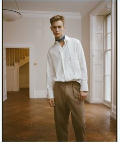 A smart vision, Oliver Houlby wears a strap-detail cotton-poplin shirt, logo-print chinos, and a multicolored logo-intarsia belt (worn as scarf) by Valentino.