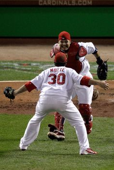 Jason Motte #30 and Yadier Molina #4 of the St. Louis Cardinals celebrate after defeating the Texas Rangers 6-2 to win the World Series in Game Seven of the MLB World Series at Busch Stadium on October 28, 2011 in St Louis, Missouri.