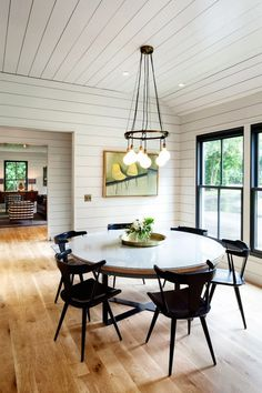 Contemporary dinning room with circular table, wood chairs, and an intricate tangled wire chandelier