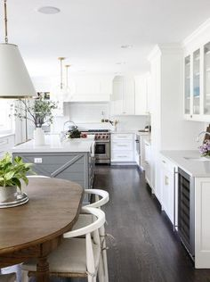 U-shaped white and gray kitchen boasts dark stained oak floor complementing a gray shiplap island topped with a white quartz countertop finished with an island farmhouse sink paired with a polished nickel gooseneck faucet illuminated by Katie Acorn Pendants.