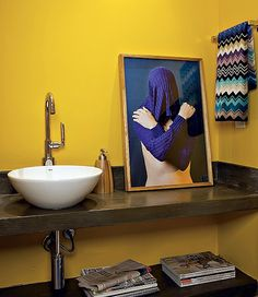 O amarelo do lavabo ganhou contraste com a fotografia de Nino Cais, apoiada sobre a bancada. Projeto da arquiteta Gabriela Marques