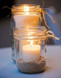 Mason jar centerpieces could de a few if these in the tables grouped around flowers. Could take sand from the beach where we get married and use this for the