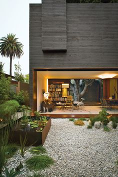 Contemporary architectural home exterior - Black wood siding with gravel garden yard - Cor-ten Steel planter boxes - Arid landscape / Desert garden