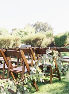 Drape greenery along the rows of chairs for decoration at an outdoor garden ceremony. #GardenWedding #WeddingDecor #OutdoorWedding