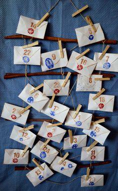 Adventní kalendář a ozdobnými obálkami, pověšenými na žebříku ze skořicových tyček.