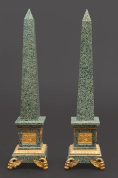 """Pair of dark green speckled with black dots """"Nero Impala"""" granite obelisks in the Empire-Style with gilt bronze mounts. The base stands at the front on two eagle forming feet to thecomposition, the square base decorated with antique-relief scenes on three of its sides - with egg & dart straight garland. Dim. H. 87 cm, 18.5 x 18.5 cm."""