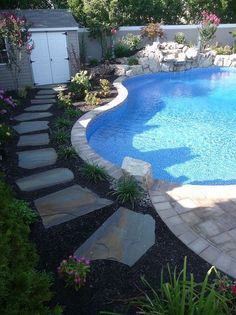 raised patios flower beds and waterfall make backyard appear