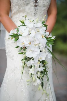 Teardrop/Cascade/Waterfall Bridal Bouquet Showcasing: White Phalaenopsis Orchids, White Dendrobium Orchids + Several Varieties Of Greenery & Foliage