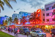South Beach Ocean Drive, Miami Florida. people enjoy Palm trees and art deco hotels at Ocean Drive by night. The road is the main thoroughfare through South Beach in Miami, USA.
