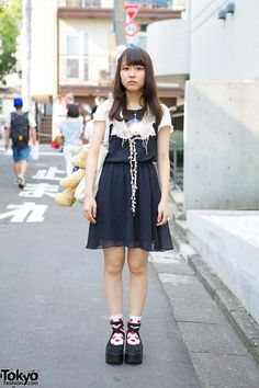 Meet Kayoko, a 17-year-old student was snapped in Harajuku. Kayoko is wearing a H&M dress accessorized with a crochet collar and a porcelain face necklace. Her tote bag features a large teddy bear, and it's a remake. Her shoes are cross strap rocking horse shoes from Tokyo Bopper, worn with heart print socks. She is also wearing a delicate ring and seashell hair pins, and her accessories are from her favorite shop, Itazura Tokyo. (Tokyo Fashion, 2014)