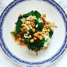 Delicious vegetarian recipe for baked sweet potatoes with creamed cashews, chickpeas, pine nuts and wilted spinach. Healthy and tasty!