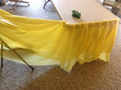 how to make a table skirt out of a plastic dollar store table cloth... uses 4 table cloths for what looks like a 6-foot table
