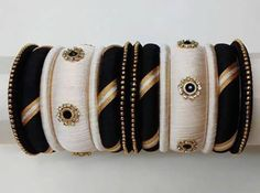 This bangle set is made of black, white ,golden silk thread, white and golden beads and black stones in eye-catching color and design. This creation will surely add ethnic look to your attire and a flawless match to wear during festive season. Silk Thread Bangles Design, Silk Bangles, Silk Thread Earrings, Bridal Bangles, Thread Jewellery, Indian Bangles, Indian Jewelry, Beaded Bracelets, African Bracelets