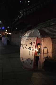 It is cold in Seoul in the winter, but people must still work. Here a professional soothsayer has set up a plastic tent to help keep himself and his customers a little warmer.