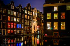 The so called Red Light District of Amsterdam is in fact one of the oldest and most beautiful parts of the city. The combination of narrow cobbled streets water canels and colorful windows make the atmosphere unique and fascinating. There is only one question - what happens behind these windows?  Single exposure  just basic development from raw.  Sony A7 with Leica M Elmar 24mm Asph.