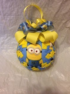 This ornament is made from Minion fabric featuring a little guy on the front and back. It is accented with yellow and topped with blue and yellow