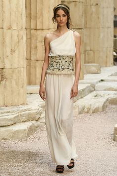 Loose cream column conjures up visions of ancient Greek princesses. Loose bodice has a single shoulder gathered and held with a gold pin. The tall waist is a gold encrusted tapestry, rolled at the bottom. The skirt below falls in loose folds to just above the floor. Black sandals. Woven gold headband. Style Planet | Chanel Cruise 2018 #haute fashion #Chanel resort #Grecian goddess dress