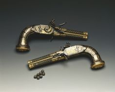 A pair of gold inlaid double barrel (turn barrel) flintlock pistol crafted by Nicolas Noel Boutet of the Versailles Armory. Presented to George IV from Louis XVIII after the defeat of Napoleon Bonaparte.  from The Royal Collection Trust