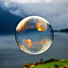 Morning light reflected in a soap bubble over the fjord, photograph by Odin Hole Standal