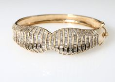 Lot# 1002 A 14K yellow gold and diamond hinged bangle bracelet. 14K yellow gold, set with 440 baguette-cut diamonds totaling approximately 13 carats, and graded J-K color and I clarity, 7'', 40 gms, est: $600/800 *Price Realized: $1,440.00