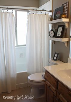 shelving above master toilet and I like the doube shower curtain idea