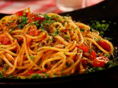 Guy Fieri drive ins (Italy recipes)This is not just any spaghetti and tomato sauce. Garlic, capers, anchovies and beautifully ripened cherry tomatoes make up this simple meal. It's like tasting all of Italy in one dish.