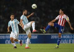 Argentina's Gonzalo Higuain (C) vie for the ball with Paraguay's midfielder Cristian Riveros next to Argentina's Paulo Dybala (L) during their Russia 2018 World Cup football qualifier match in Cordoba, Argentina, on October 11, 2016. / AFP / Juan Mabromata