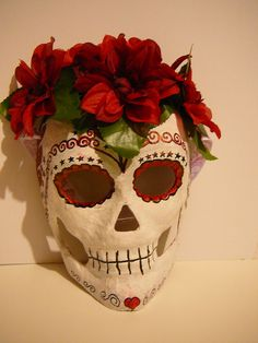 The American Dead mask. This mask uses traditional Dia De Los Muertes themes but also incorporates red, white and blue to show how many Mexican Americans relate to both Mexico traditions and American patriotism. This mask can be yours, just visit my Etsy store, only $10.