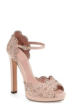 Polished studs and dainty floral cutouts add feminine flourishes to this stunning Alexander McQueen platform sandal.