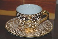 It was produced by a French maker widely recognized for its fine porcelain, which is painted entirely by hand.The gold is stunning. The white design is raised a little bit. On the bottom are words written in French. Tea Cup Set, Cup And Saucer Set, Tea Cup Saucer, Vintage Tea, Yellow Cups, Antique Tea Cups, Gold Cup, Vases, Teller