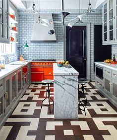 """""""Just as the fireplace is the center of the living room, the stove is the center of the kitchen. I always like to highlight it rather than conceal it. This Lacanche range looks sharp in a dynamic orange."""" 