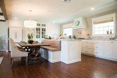 The new kitchen footprint took up more area than the original, so to save space, we designed an island that would double as bench seating for the dining room table. This made enough area for both a dining room and a kitchen large enough for entertaining.