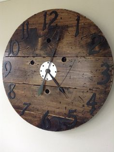 This Clock head originated from an old wooden cable reel or wire spool. Sanded, Stained in a Dark Walnut and roughed up for a Rustic look. Numbers are