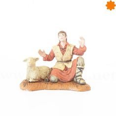 Joven pastor con oveja sentados adorando al niño Jesus