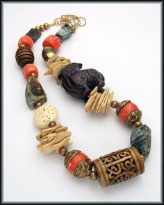 Materials: handcarved foo dog focal, natural chrysocolla nuggets, handmade Tibetan beads, handmade African brass beads, vintage wooden beads, carved wooden bead, carved Jade bead, handcarved bone beads, silk cord, bronze wire, brass chain