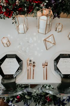 Clear chargers, black octagonal plates, gold utensils, and geometric candle holders | Image by Jessie Schultz Photography