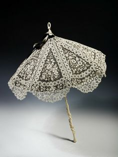 The parasol was a popular accessory during the 19th century, a period before the sun-tanned face became fashionable.  Many parasols were made of lace, and like this example, lined with a contrasting silk to show off the design of the lace and enhance its sun-shading properties.    The handle is made of elephant tusk ivory.