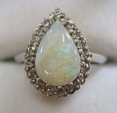 A two-carat opal is surrounded by lovely diamonds all set simply in white gold. The opal has shades of blue and green Diamond Gemstone, Diamond Pendant, Diamond Jewelry, Diamond Rings, Opal Rings, Gemstone Rings, Black Diamond Engagement, Engagement Rings, Cheap Wedding Rings