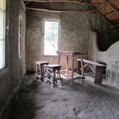 #Inneneinrichtung einer #Lehmhütte um 1920- mit #Feuerstelle auf dem #Lehmfußboden und abgegrenztem #Schafstall im Bild rechts. #Interior