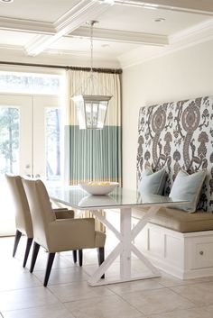 Love the color-blocked window treatments and built-in banquette in this aqua and white  breakfast area.  Designed by Tobi Fairley.