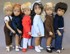 "A grouping of 15"" vinyl early pre-Trendon English Sasha dolls, Untied Kingdom, 1968-1970, by Frido. From left: Sasha Blonde Dungarees, Sasha Redhead Ballet, Gregor Fair Pyjamas, Sasha Gingham Brown Hair, Sasha Blonde Brown Cord, and Gregor Dark Denims."