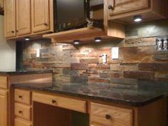 Layered slate tiled backsplash with Uba Tuba granite kitchen counter.