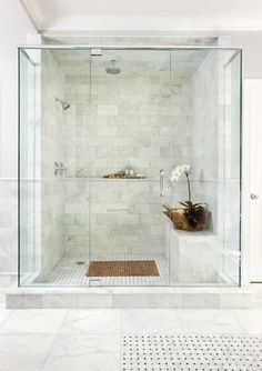 A full width shower plinth for the luxurious bathing rituals. Create a rich and practical aesthetic with double shower heads and full height tiling, glass, monochromatic palette.