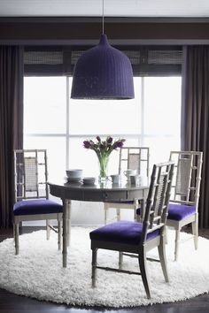 Purple and gray dining room with round gray bamboo dining table, gray bamboo dining chairs with purple velvet cushions, white round flokati rug, Ikea Leran Pendant painted purple, chocolate brown walls and brown curtains with lilac trim.