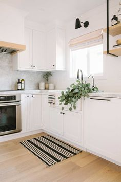 Cocina blanca con suelo de madera. Los toques negros del aplique, la estantería y la alfombra le dan personalidad. #cocinas #cocinablanca #suelomadera